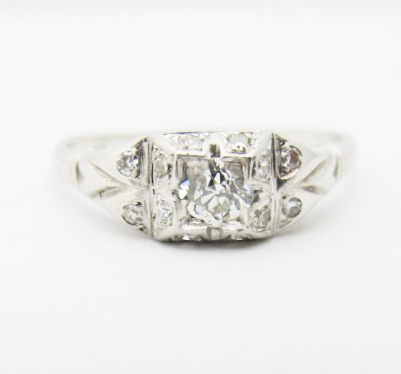 14k white gold setting with diamond accents.  Center stone is  0.19 carat I color, SI1 clarity old European cut diamond. Art Deco, c.1920s.
