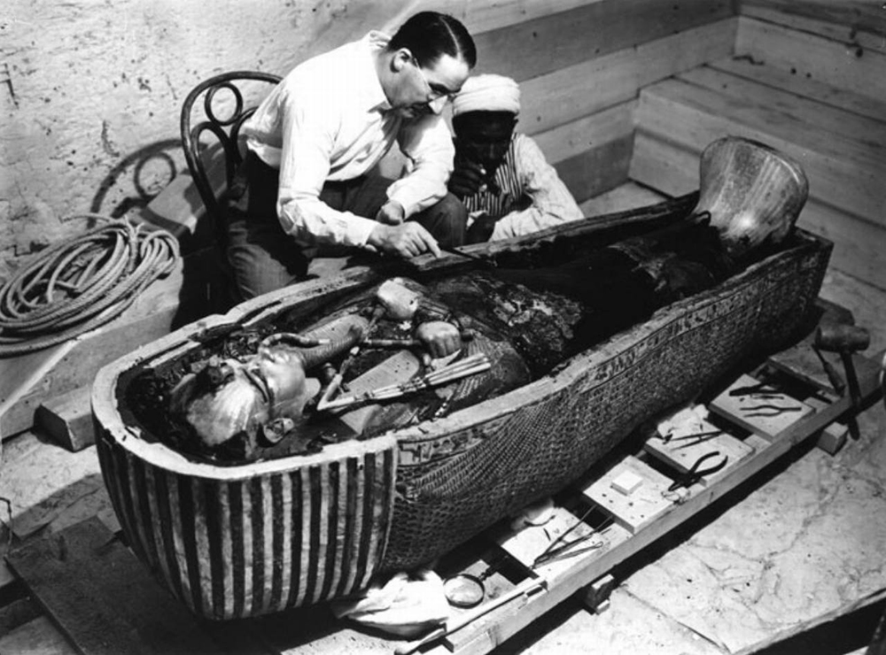 Howard Carter exploring King Tut's sarcophagus.