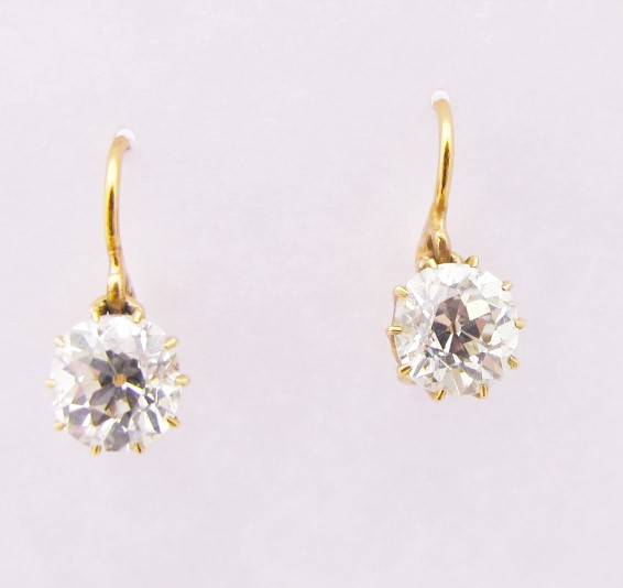 Pair of 1.30ct J/VS2 old mine cut diamonds in rosey 18k yellow gold settings. c. 1900.