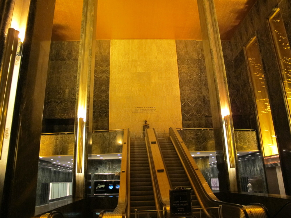 The escalator replacing what would have been a grand staircase. Both an example and a metaphor for the period.