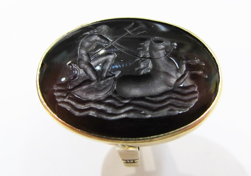 Antique onyx intaglio set in yellow gold ring, featuring a miniature scene of Poseidon.
