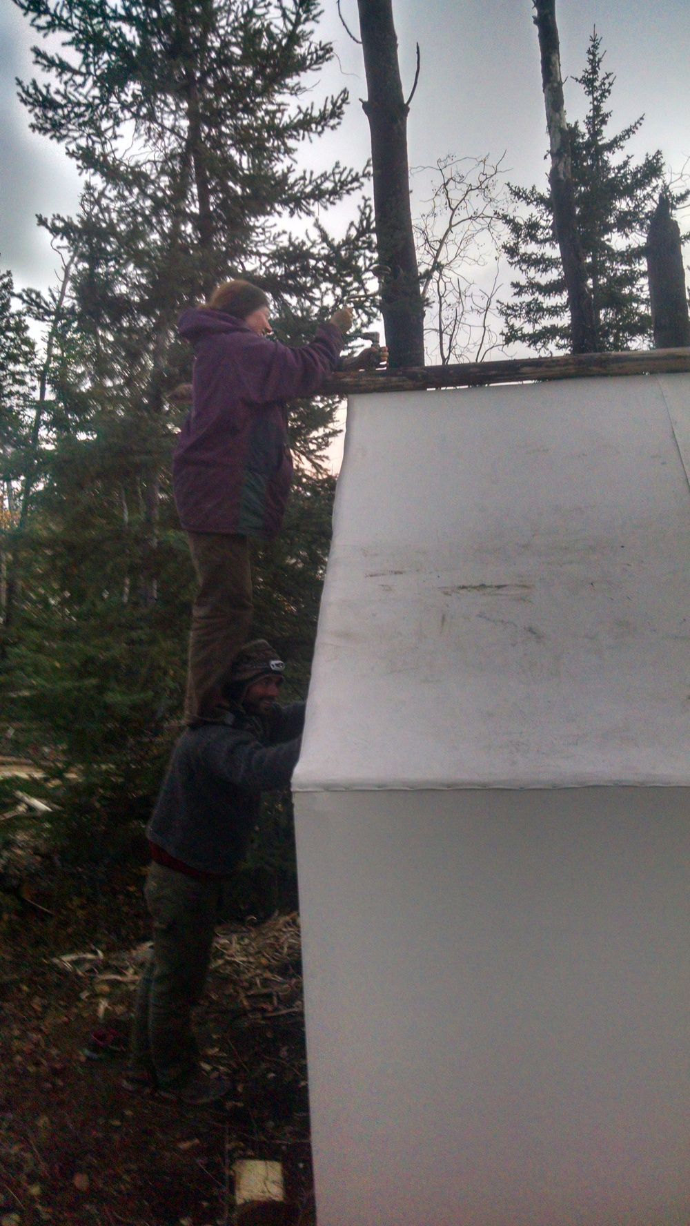 "David the ""Human Ladder""for Jenna so she can reach the peak to lag bolt the second ridge pole in place."