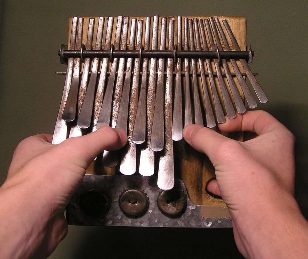 The Mbira is a thumb piano that resembles the Kalimba. It is made up of two rows of metal strips that come in staggered dimensions. They are placed on a wooden resonator (sound box). It is most common in East and Southern Africa. The countries include Namibia, Zambia, Swaziland, Zimbabwe, and Tanzania.