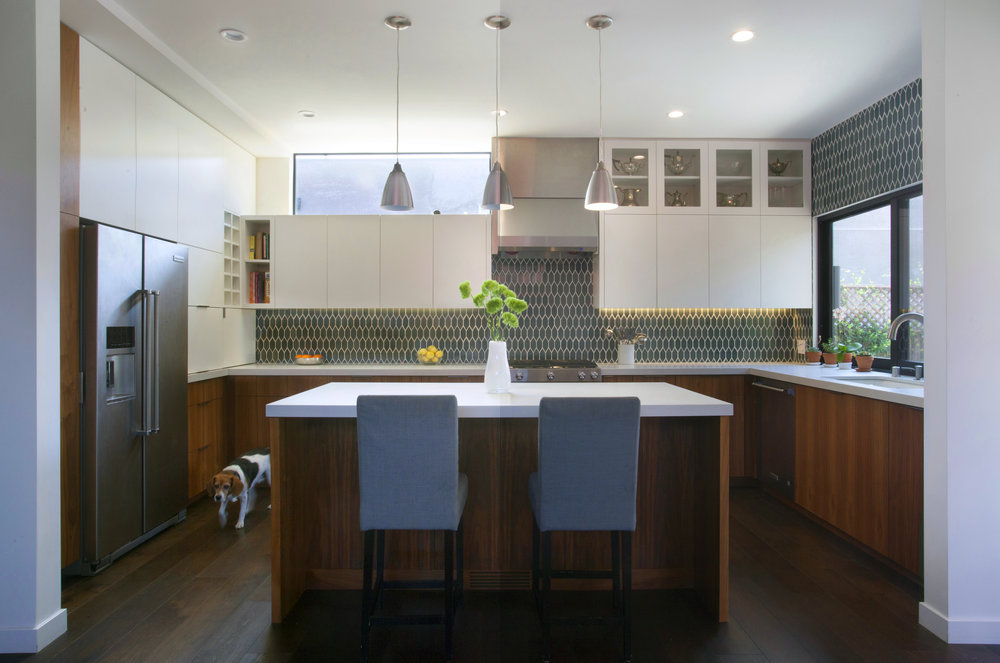 The kitchen features Walnut lower cabinets paired with high-gloss white cabinets above. Heath ceramic tile and Caeserstone countertops complete the look. Large windows to the south connect the kitchen to the backyard, while a clerestory window washes the space with morning light.