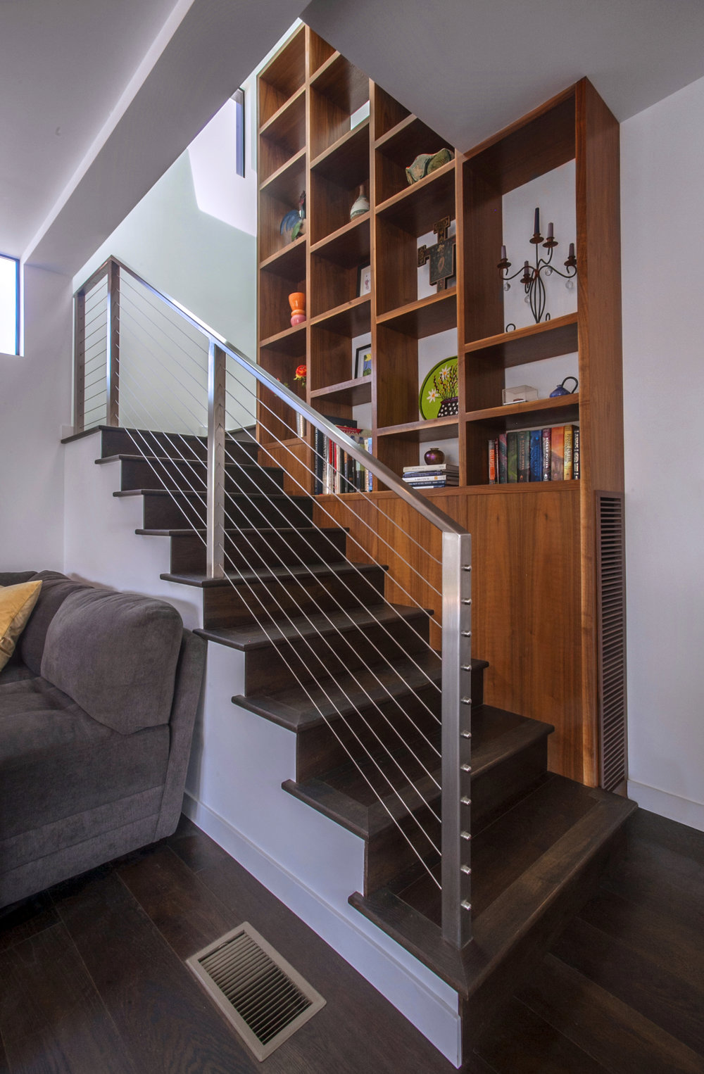 The new staircase, with an integrated custom walnut bookshelf in the center of the switchback and three large skylights above, links the two floors.