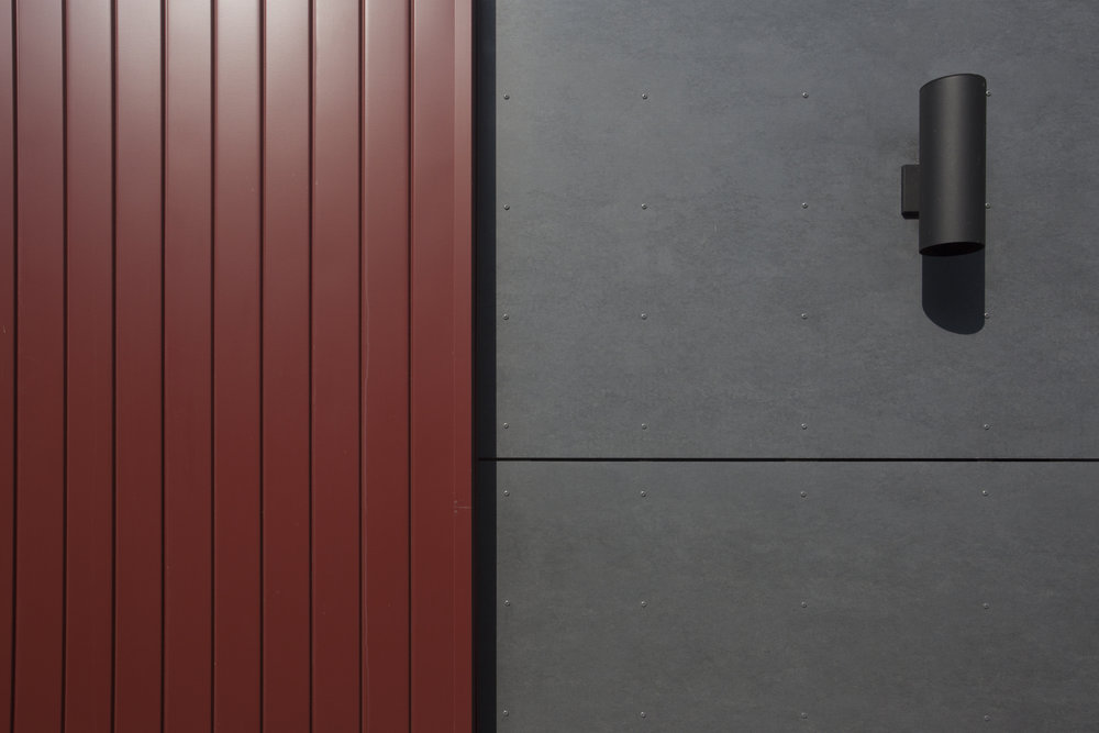 Red metal siding panel transitions to dark grey cement board.