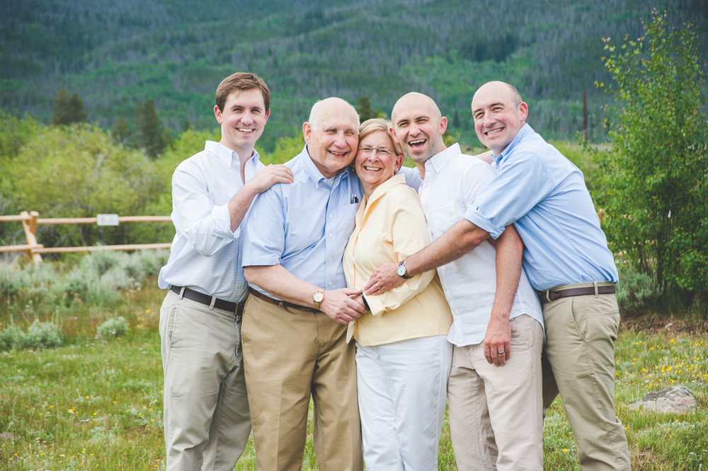 Mom, Dad and three grown sons all hug in tight for a sweet, intimate family photo during vacation in the mountains of Colorado.