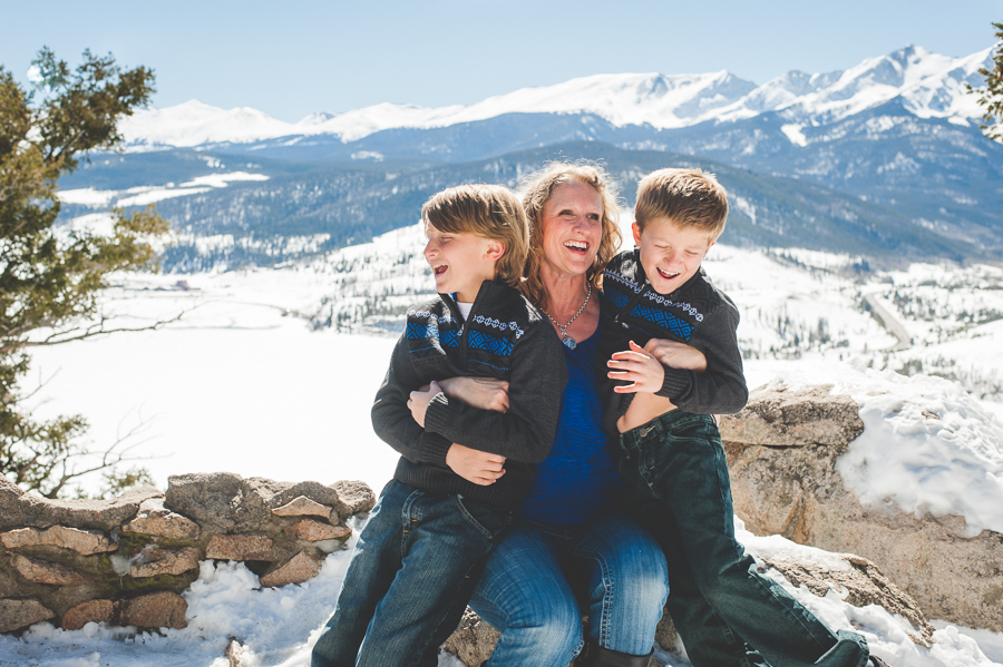 Tickles and giggles break out during a winter family photo shoot in the mountains, overlooking Peak One and Lake Dillon near Breckenridge, Colorado. Mom and two sons.