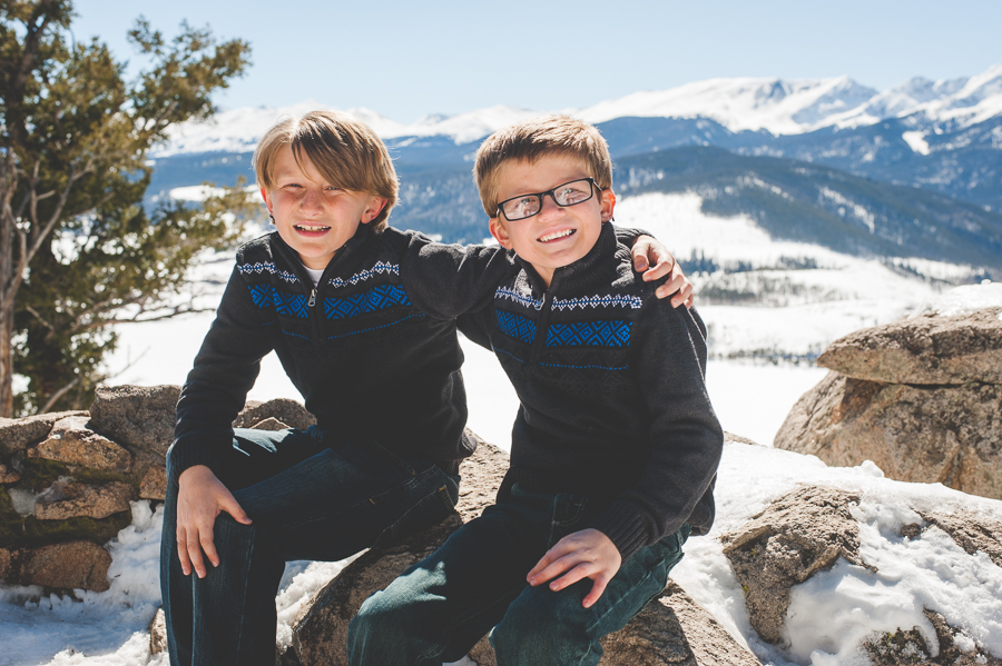 Brothers in matching sweaters (cute!) put arms around one another for a sweet family photo session in the snowy mountains of Breckenridge, Colorado.