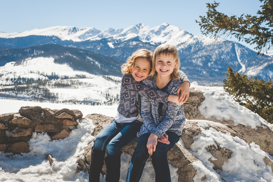 Younger sister hugs older sister during a winter photo shoot in the mountains near Breckenridge, Colorado. Peak One and Lake Dillon are in the background.