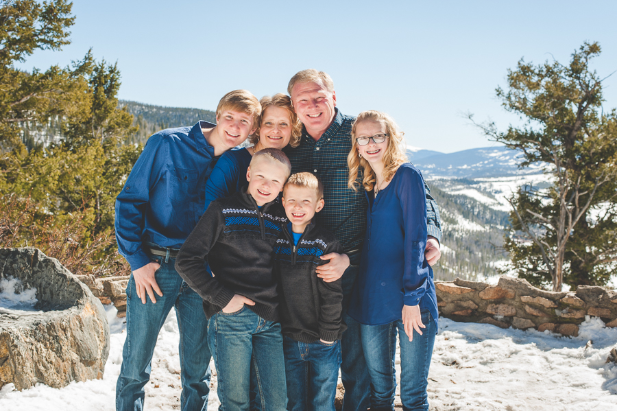 A family of six gathers close for their portrait at Sapphire Point, near Breckenridge, Colorado, with snow covered ground and mountaintops in the background.