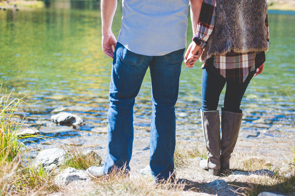 couple holds hands at the edge of a mountain lake near Breckenridge, Colorado during their destination engagement photo session