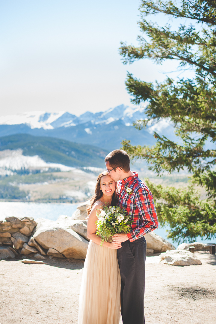 A Colorado elopement at Sapphire Point with snowy, white peaks behind the couple and a warm, autumn sun shining.