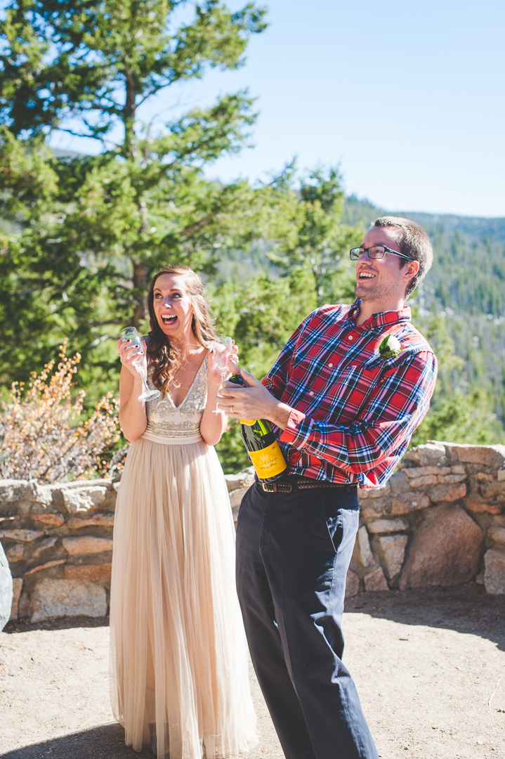 A Colorado groom pops the cork on the champagne after their intimate elopement at Sapphire Point. | Keeping Composure Photography