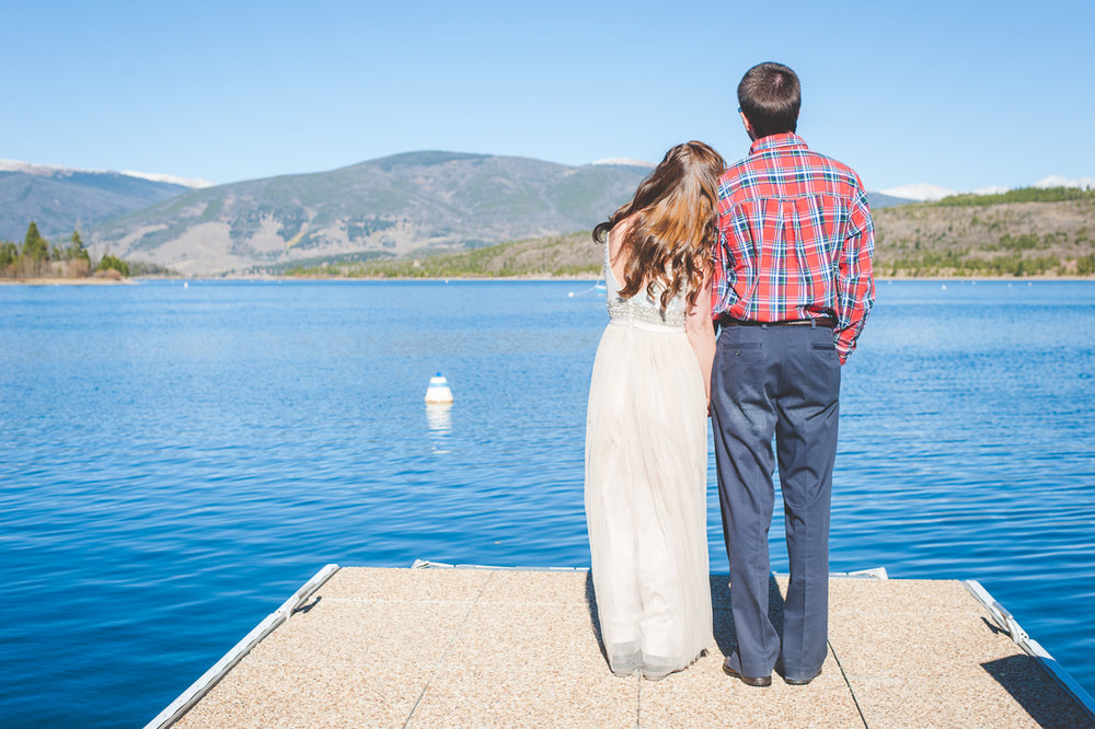 Colorado bride and groom take a moment to look out across the lake and the mountains after their intimate elopement.