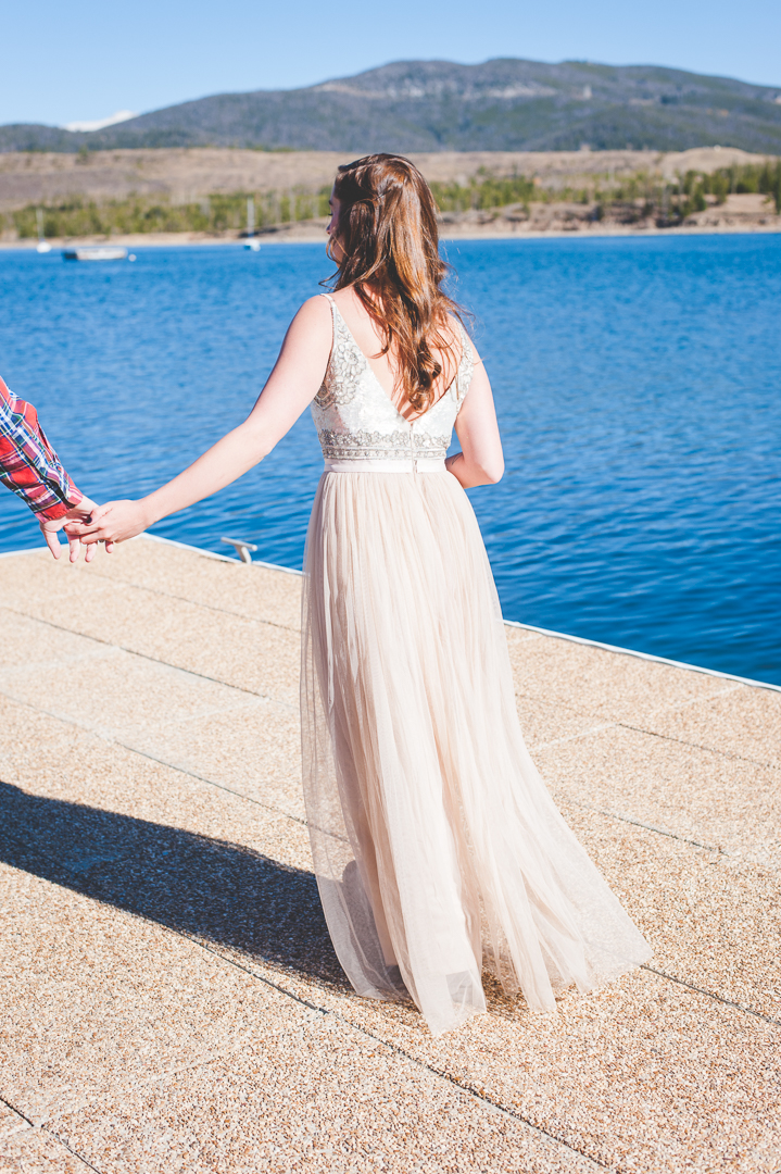 Beautiful back of this wedding dress against the blue Lake Dillon in Colorado. | Keeping Composure Photography