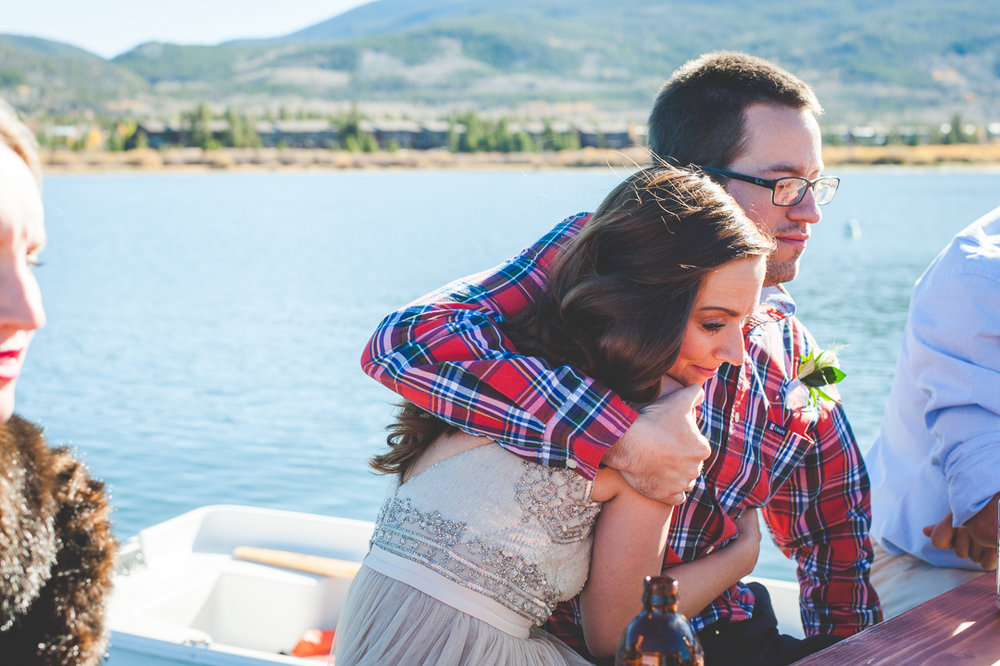Groom dressed in plaid squeezes his new wife close to him, after a stunning autumn elopement at Sapphire Point in Colorado. Casual celebration ensued at a picnic table on the docks of the Frisco Marina. | Keeping Composure Photography