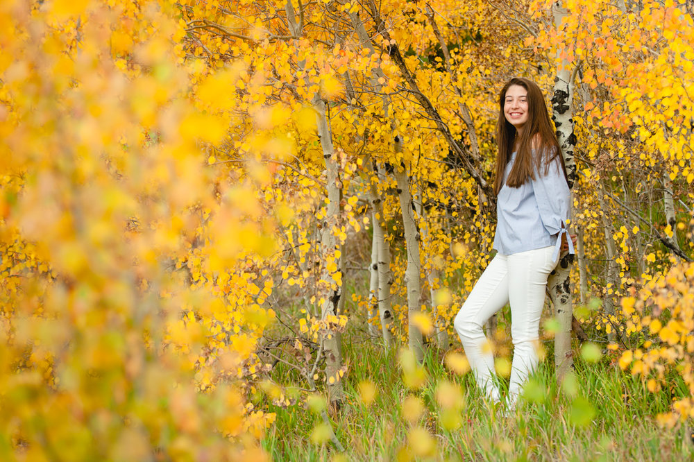 High school senior girl poses for her senior photos in the middle of yellow aspen trees. | Keeping Composure Photography