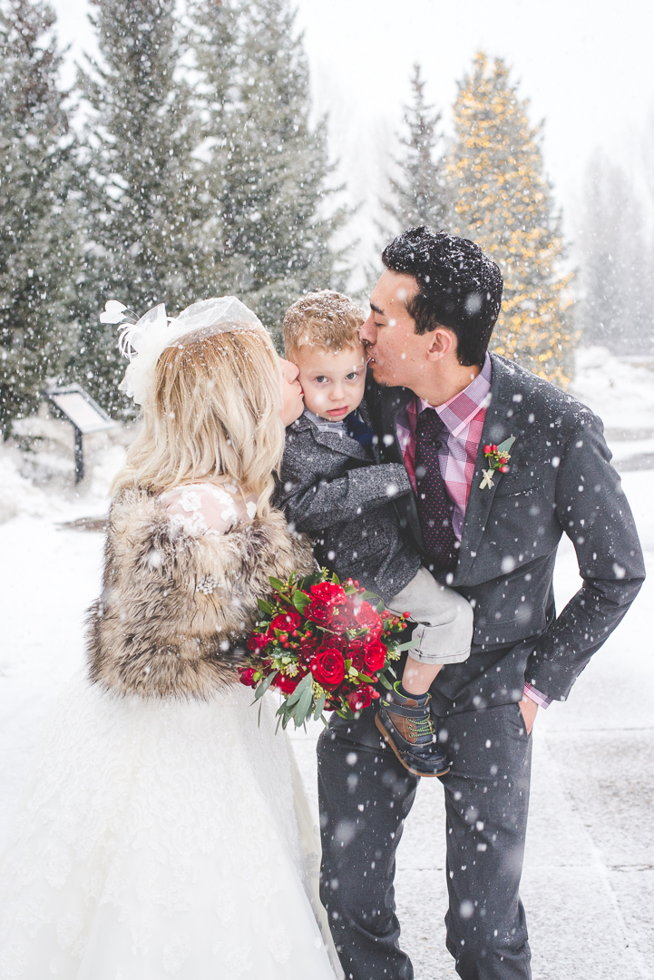 Mom and Dad (Bride and Groom) give their son a quick kiss in the snow before continuing with their elopement photos. | Keeping Composure Photography