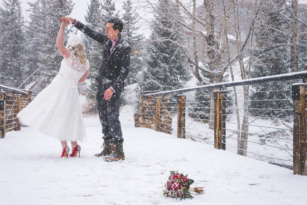 When it snows on your wedding day, Dance! Red accents pop on the white snow in this Breckenridge, Colorado elopement. Red nails, red flowers, red shoes and red lips: winter magic. | Keeping Composure Photography