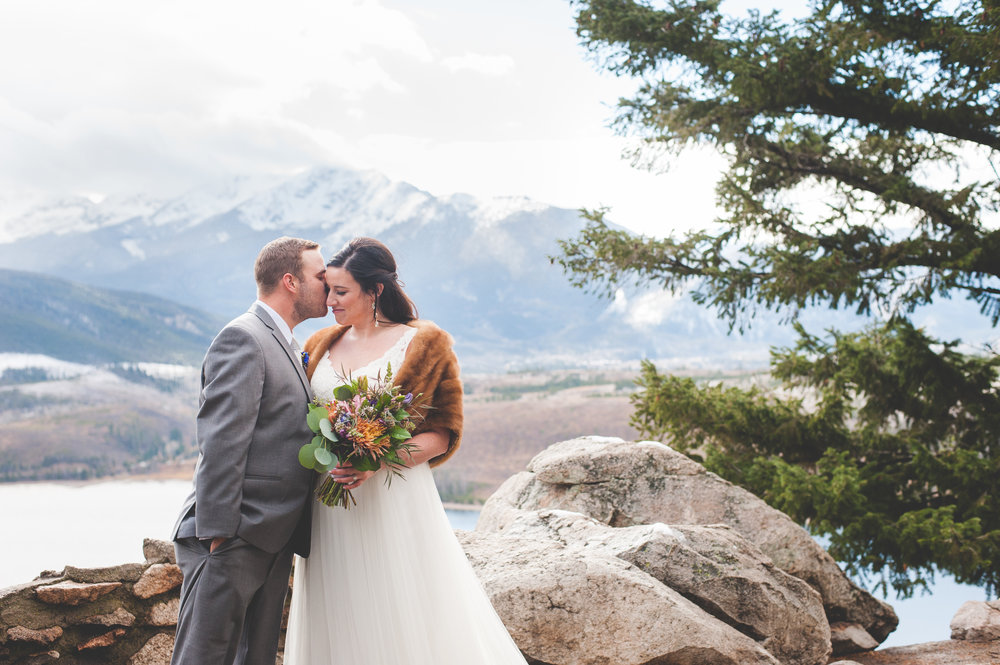 A Colorado bride and groom romantically embrace after their destination elopement at Sapphire Point in Dillon, CO, planned by Summit Mountain Weddings and photographed by Keeping Composure Photography.