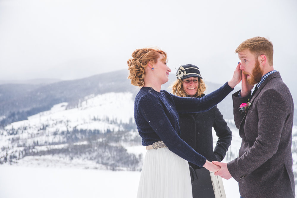 colorado winter bride wipes away a tear on her groom's face at their intimate elopement at Sapphire Point