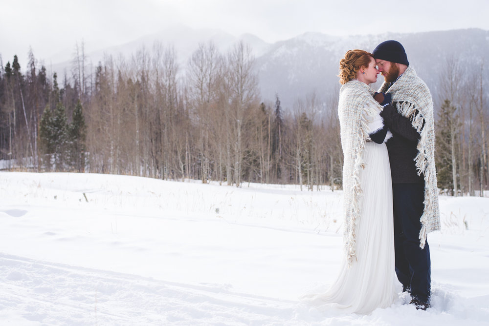 colorado bride and groom embrace under a blanket during their intimate destination elopement in colorado