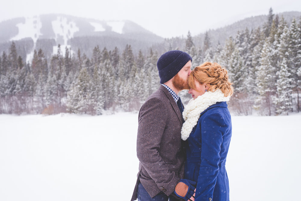 the ski runs at breckenridge hang in the distance behind the winter pond during this colorado winter elopement session