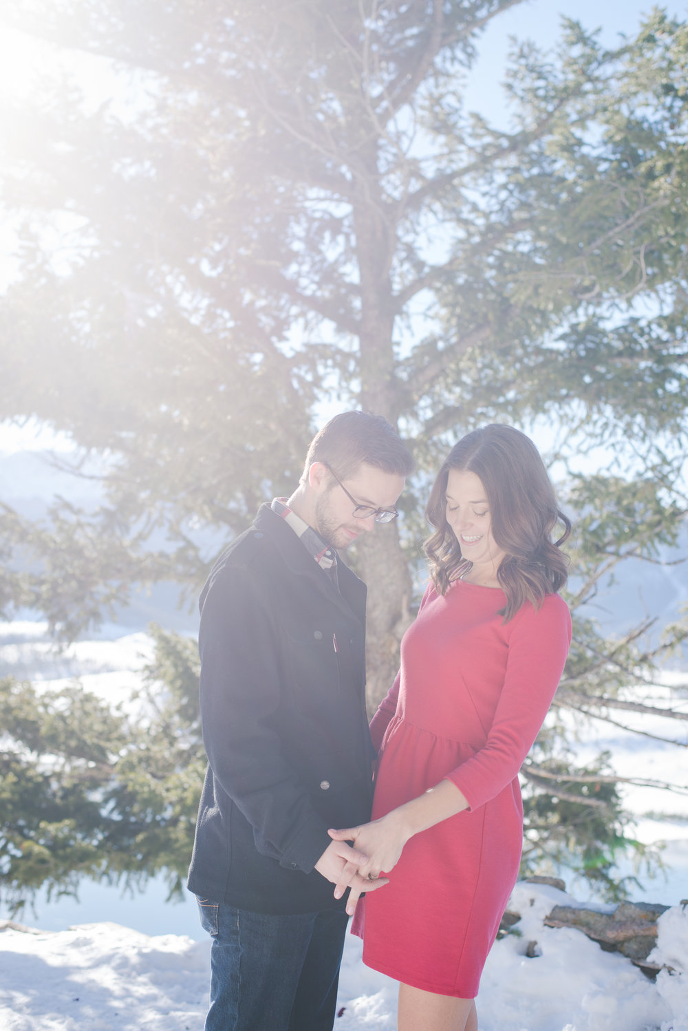 a red dress and a nice coat compliment one another during this winter engagement shoot in colorado