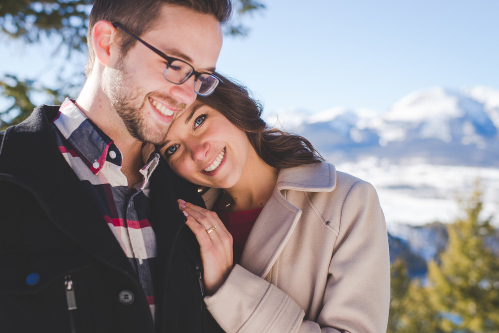 a sweet pose with mount buffalo in the background, during this classic winter engagement photo session at sapphire point in dillon, colorado