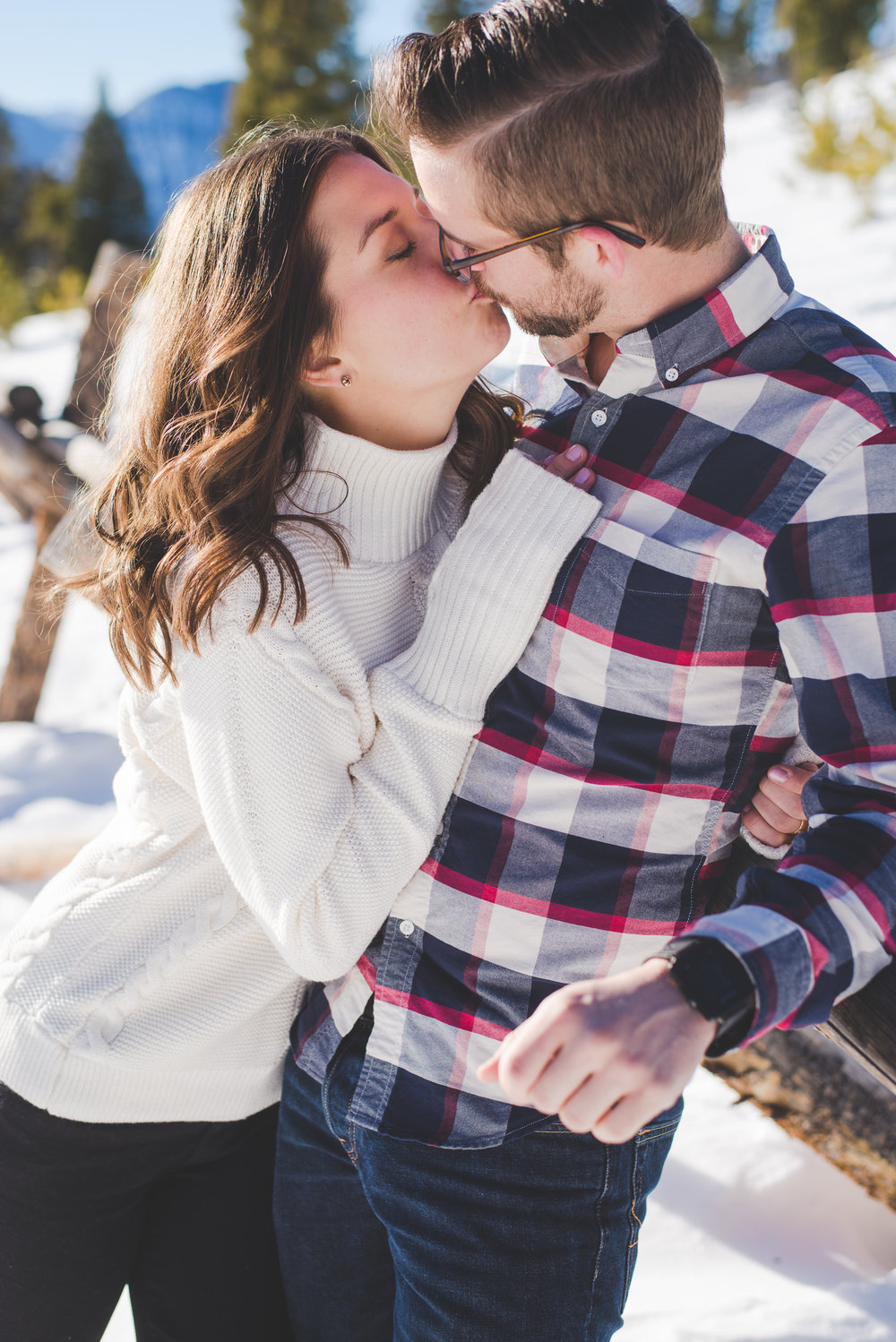 chilly weather means more snuggles and kisses! this couple got close and romantic during their winter engagement session in the colorado mountains. and their style? nailed it!