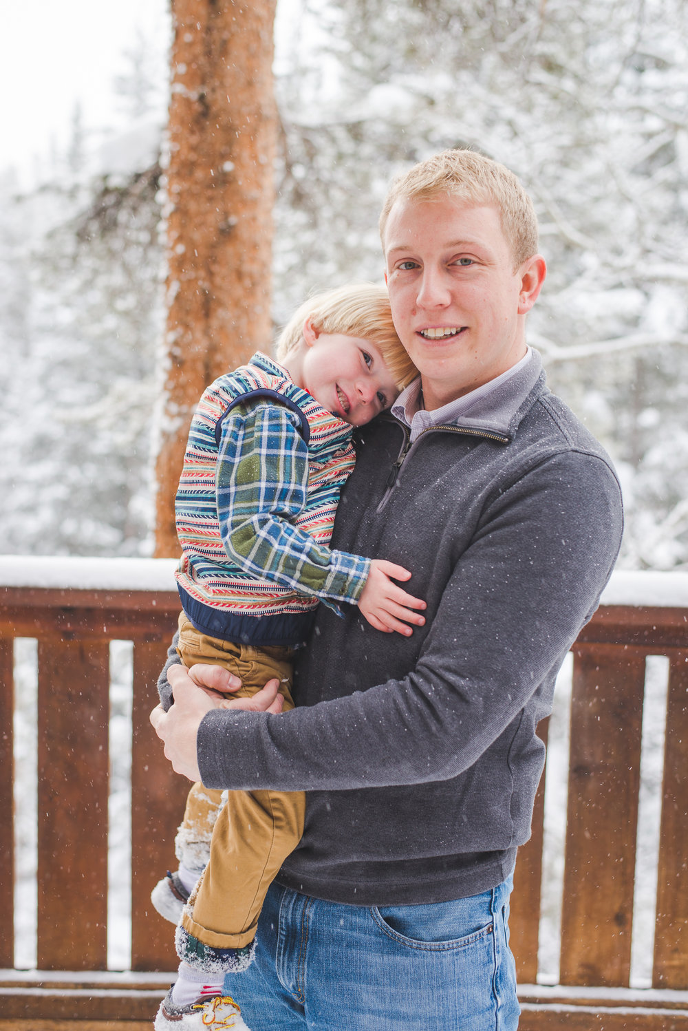 dad gets a little smile out of his son for their winter family photo shoot in Breckenridge, Colorado