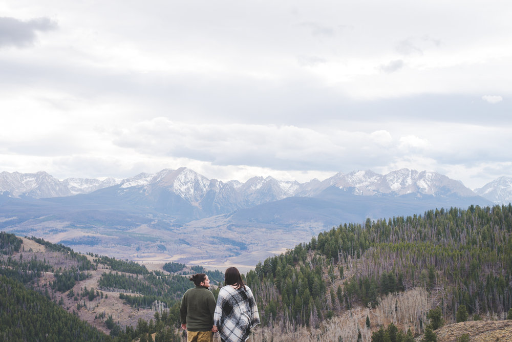 overlooking a stunning mountain range in colorado during this couple's adventure engagement session