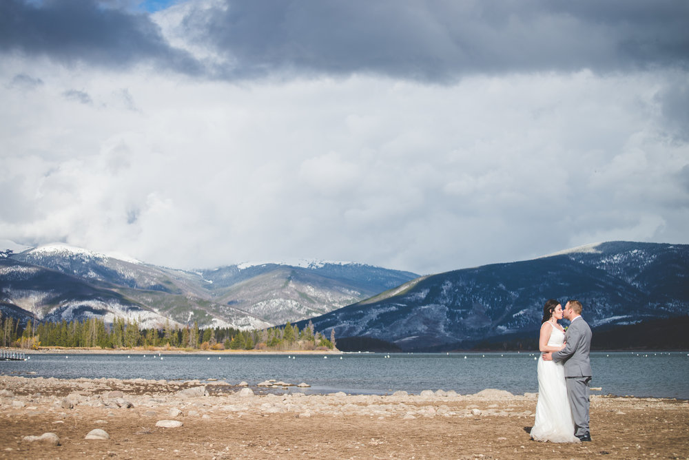 Low waters allowed this bride and groom to hike down to the lake bed, while low clouds and new snow sprinkle the mountains in the background