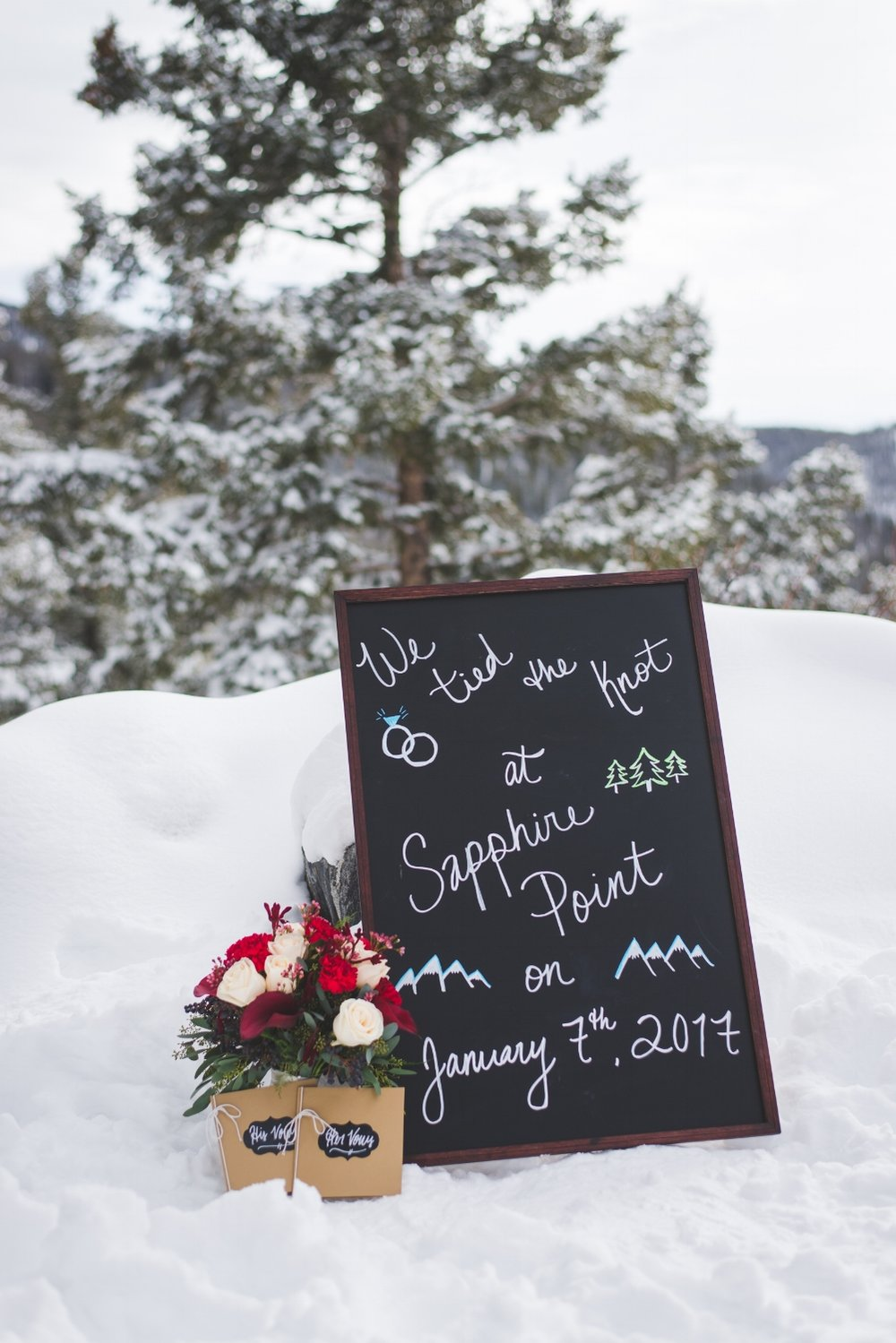 adorable details at the winter elopement at Sapphire Point: sweet vow books, beautiful flowers and a unique chalk board sign commemorating the wedding date.