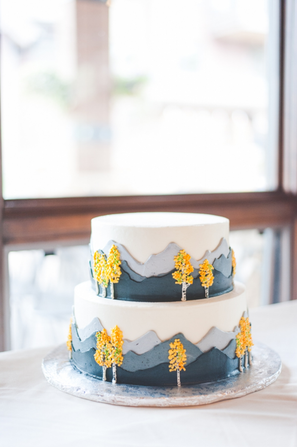 beautiful details on a simple cake for a Breckenridge mountain wedding, complete with yellow aspen leaves and mountain landscapes