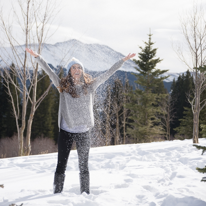 excited girl throws snow up in the air in Breckenridge, Colorado