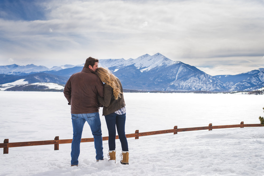 these two cozy up together to keep warm and share their comfort during their winter engagement session overlooking Peak One and Lake Dillon in Dillon, Colorado