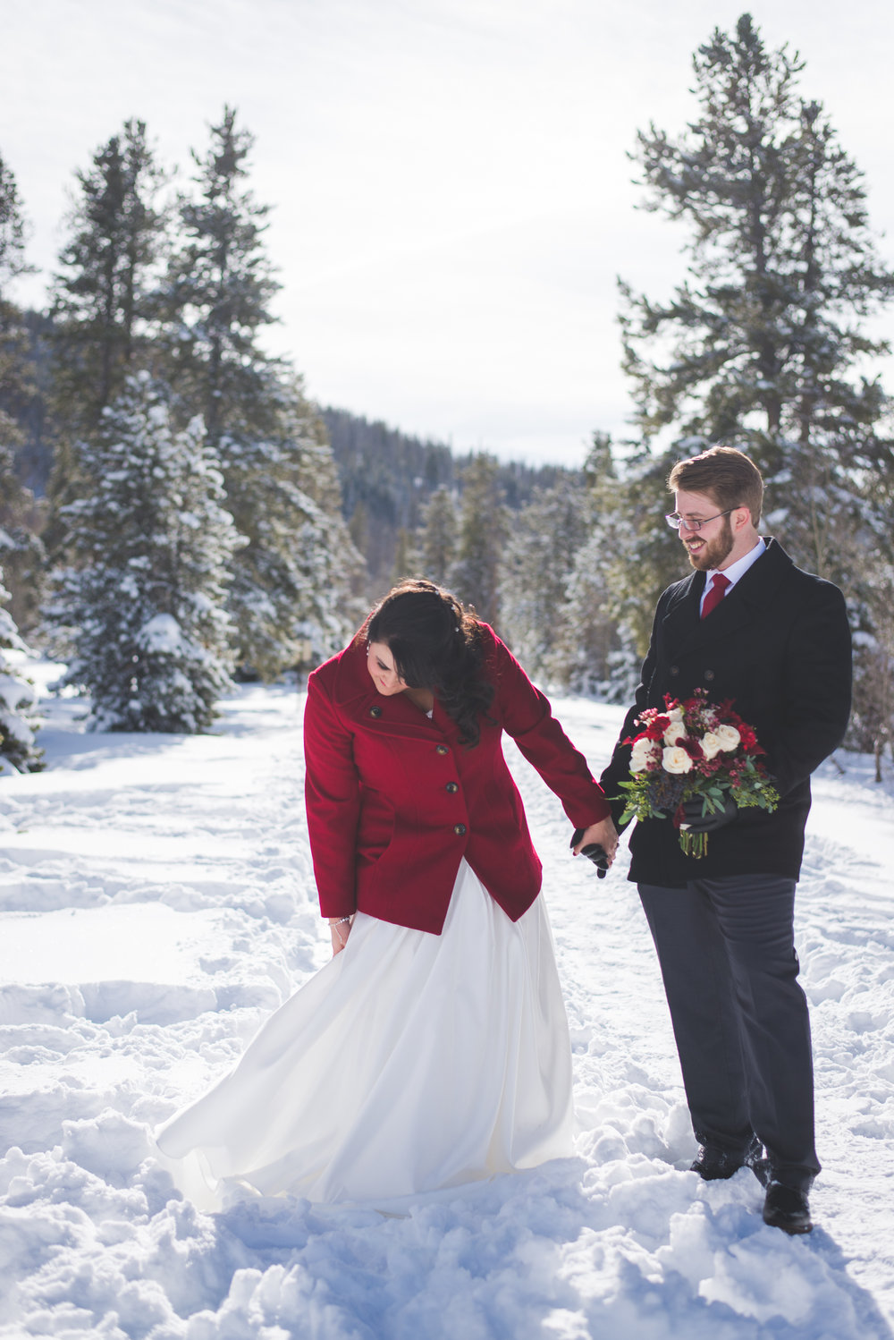 A red coat and red flowers were the perfect touch to this winter elopement wedding in the Colorado mountains.