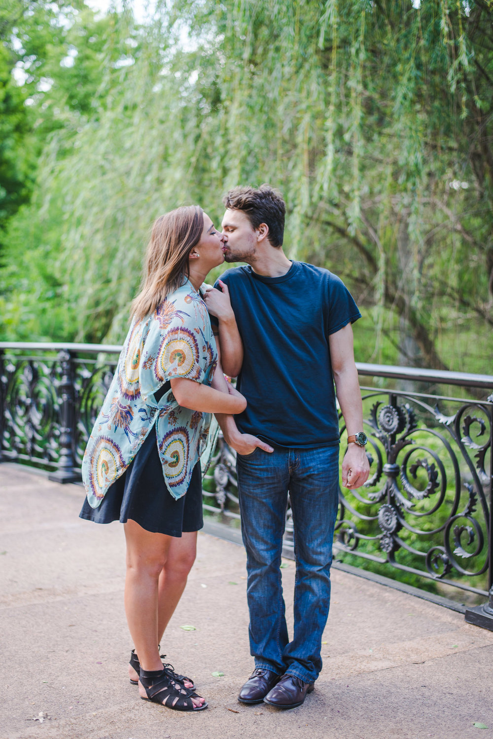 Couples portrait photography session in Lafayette Square Park in St. Louis. Black iron historic bridge and willows in the background.