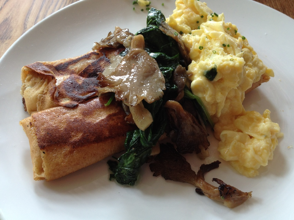 Cottage Cheese Blintzes  topped with soft scrambled eggs, oyster mushrooms and spinach.