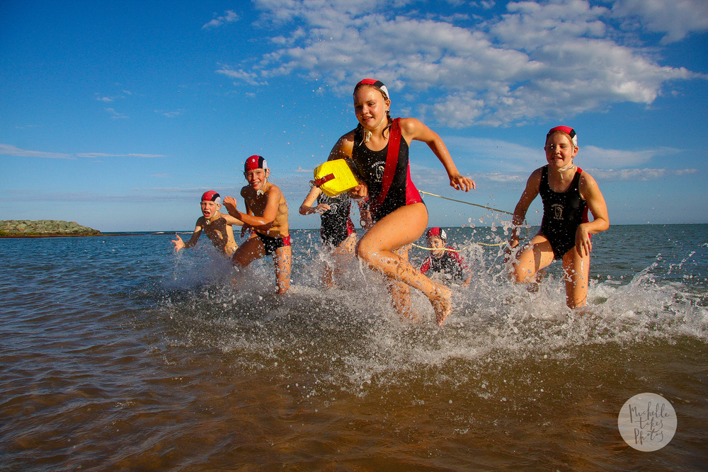 Redcliffe Surf Life Saving Club nippers run through the water during a training session.
