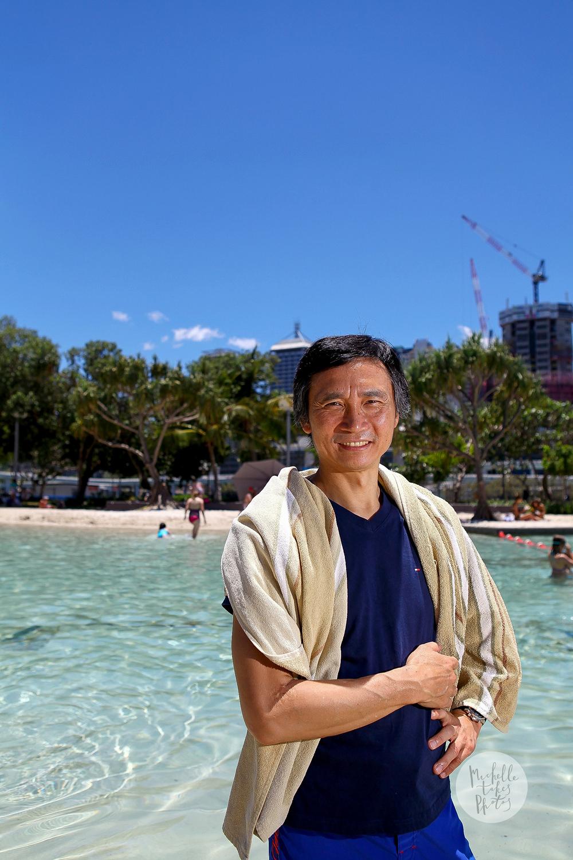 Queensland Ballet artistic director Li Cunxin enjoying the summer at Streets Beach, South Bank.