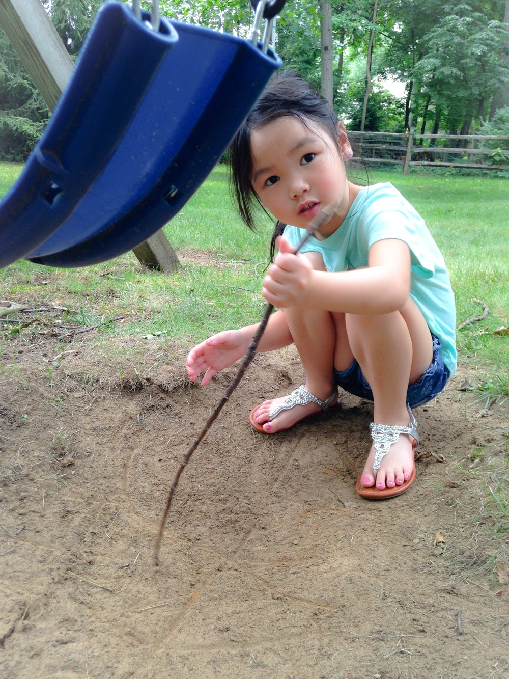 Writing letters with a stick and dirt