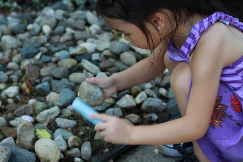 Mei creating chalked rock art.