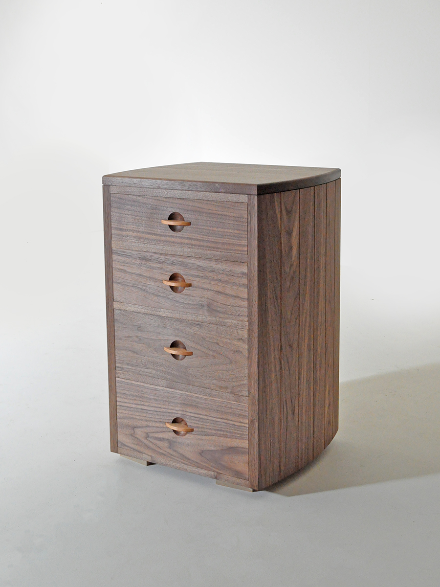 Irene Banham's Walnut Chest of Drawers with Cherry handles, and contrasting maple for the internal parts of the drawers. The overall impression of the drawers is of a contemporary style, with the curved sides giving a more sweeping and elegant shape than a simple rectangular design.
