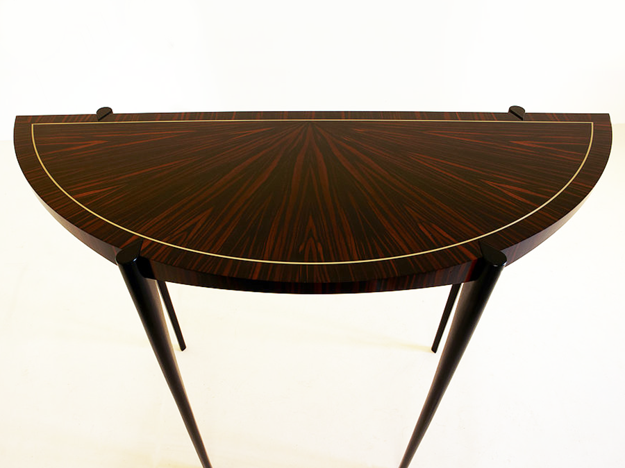 Tom Jarrold's elegant hall table in Macassar Ebony with traditional 'starburst' veneer pattern on top and incorporating an inlayed line of silver stringing. The table has a scalloped underside.