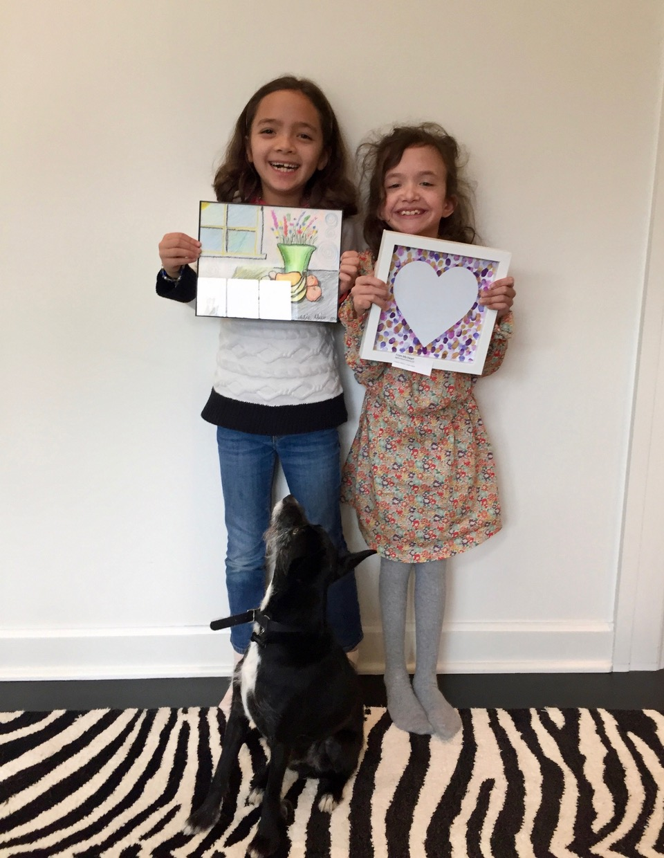 Proud artists Madeline and Agatha Holloway, McGilvra Elementary School classmates, pose with Agatha's dog Tuxedo.