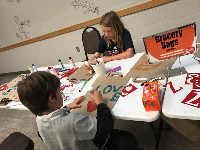 Brothers worked together to decorate grocery bags which will hold items for the local food pantry.