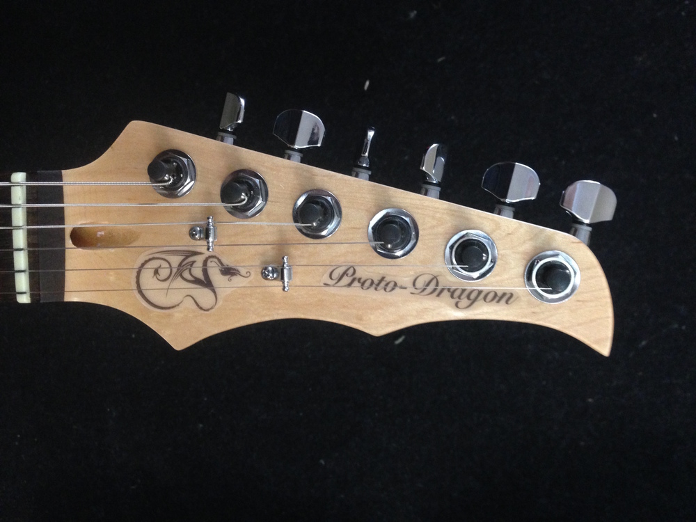 Our Dragons wing Headstock prototype with decal logo.    We will not be using stickers when it goes to production.